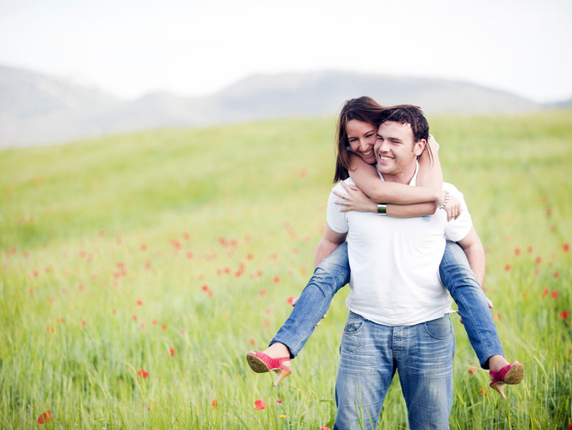 Couple Doing Piggy Back In Field